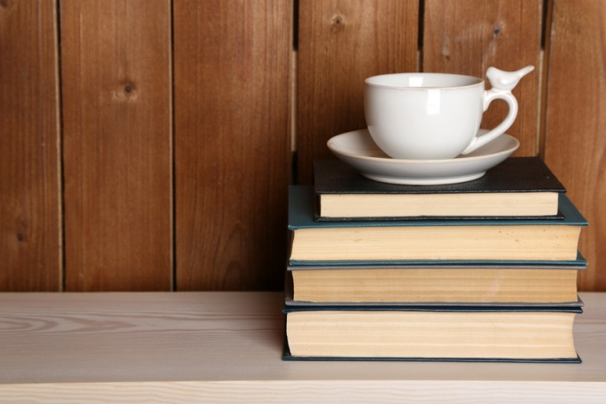 © Africa Studio / Fotolia.com -Pile of books with cup on tabletop and wooden background
